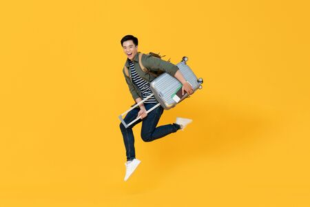 Young excited Asian tourist man with baggage jumping in mid-air ready to travel isolated on yellow background Foto de archivo