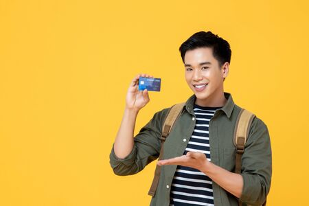Young smiling Asian tourist man holding credit card ready to travel isolated on yellow background 版權商用圖片 - 145323767