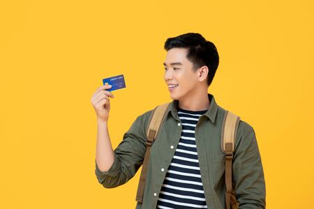 Young Asian tourist man holding credit card ready to travel isolated on yellow background 版權商用圖片