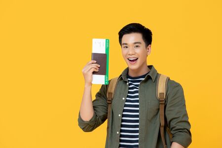 Young handsome Asian tourist man smiling and holding passport with boarding pass ready yo fly 版權商用圖片