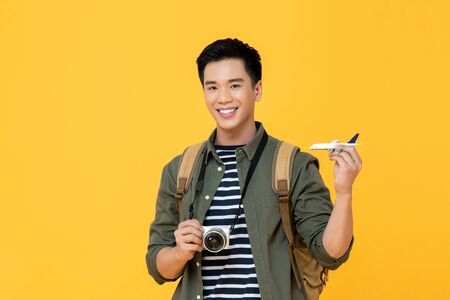 Young handsome smiling Asian tourist man holding plane model and camera isolated on yellow background 版權商用圖片