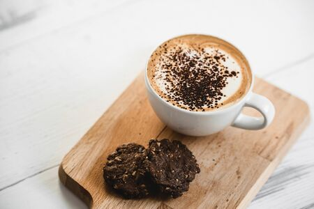 Hot latte coffee in the cup with chocolate cookies on wood platter in cafe for breakfast Stock fotó