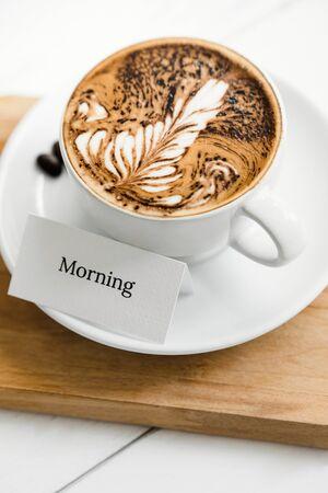 Fern pattern latte art coffee in the cup beside greeting text on wood platter in cafe Stock fotó