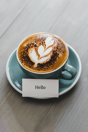 Cup of coffee with latte art and Hello greeting text on vintage wood table in cafe