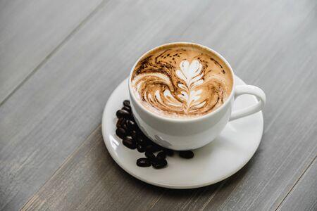 Fresh brewed coffee with fern pattern latte art in white cup on wood tabble Stock fotó