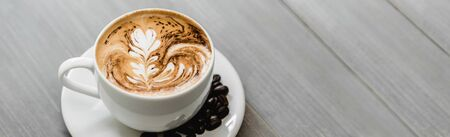 Fresh brewed coffee with fern pattern latte art in white cup on wood banner background