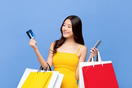 Young smiling beautiful Asian woman making online payment through mobile phone via credit card while carrying colorful shopping bags in isolated blue background