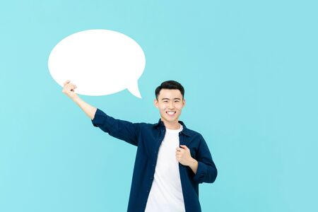 Waist up portrait of young smiling Asian man holding up an empty white speech bubble in light blue studio background Stock fotó - 145323652