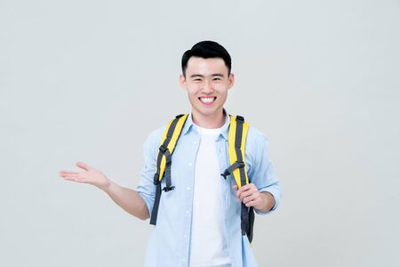 Waist up portrait of young confident smiling Asian tourist man backpacker doing  open palm gesture in gray studio background