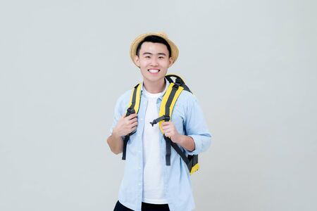 Waist up portrait of young smiling Asian tourist man backpacker holding his yellow backpack straps in gray studio background 版權商用圖片