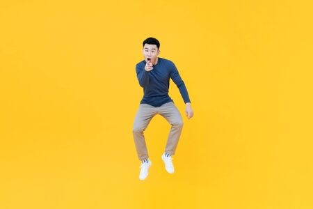 Full length portrait of young happy Asian man jumping in mid-air while in a fun pointing gesture on yellow isolated studio background 版權商用圖片 - 145323663