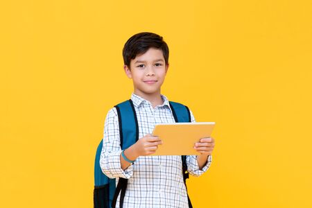 Waist up portrait of handsome young schoolboy wearing backpack holding a tablet while looking straight in camera in yellow isolated studio background
