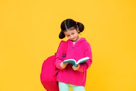 Portrait of cute pretty girl with pigtail hair in pink jacket and backpack reading book in yellow isolated studio background 版權商用圖片