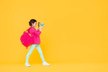 Smiling cute pretty girl with pigtail hair in pink jacket and backpack looking through a magnifying lens in yellow isolated studio background 版權商用圖片 - 145323670