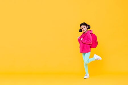 Excited cute pretty girl with pigtail hair going to school wearing pink jacket and backpack doing a one leg raise gesture in yellow isolated studio background Stock fotó - 145323673