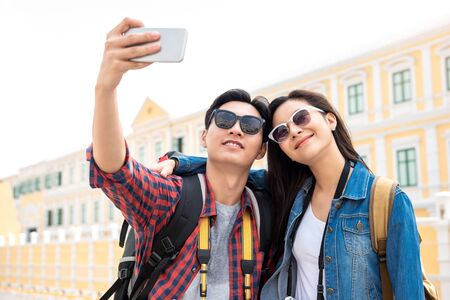Portrait of young happy Asian tourist couple in casual attire taking a selfie while traveling in Bangkok Thailand