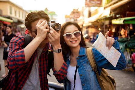 Cheerful young Asian tourist couple taking a photo while happily traveling on Khao San road at Bangkok Thailand Stock fotó - 145323691