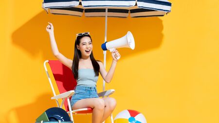 Ecstatic young Asian woman in summer beach outfit holding and announcing on megaphone in sunny yellow isolated studio background Stock fotó - 145323556