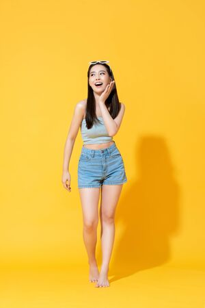 Full lenght portrait of surprised beautiful young Asian woman in summer beach outfit with palm touching face in bright yellow isolated studio background