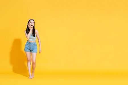 Full length portrait of surprised beautiful young Asian woman wearing summer beach outfit with palm touching face in sunny yellow isolated studio background 版權商用圖片