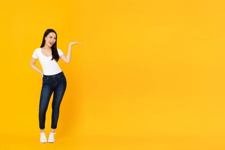 Full lenght portrait of smiling confident young beautiful Asian female model doing open palm gesture to empty space beside in yellow isolated studio background 版權商用圖片 - 145323567