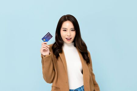 Beautiful smiling Asian woman in winter clothes showing credit card in hand for financial and cashless society concepts isolated on light blue  background 版權商用圖片