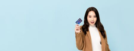 Beautiful smiling Asian woman in winter clothes showing credit card in hand for financial and cashless society concepts isolated on light blue banner background