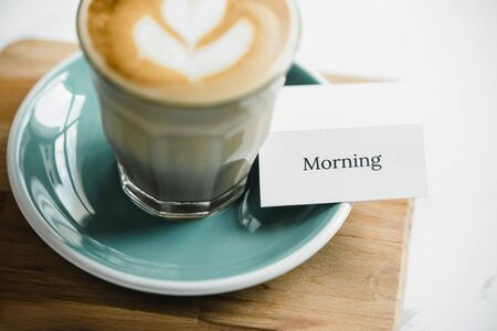Morning text table card and fresh brewed Cappuccino coffee with beautiful latte art on wooden board ready to drink