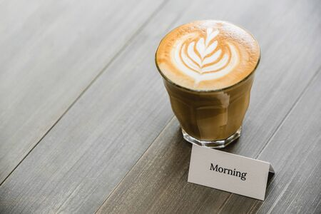 Fresh brewed coffee in tumbler glass with beautiful latte art on wooden table ready to drink