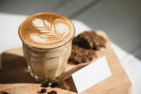 Fresh brewed Cappuccino coffee with beautiful latte art on wooden platter ready to drink