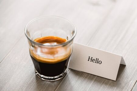 Fresh brewed Espresso coffee shot in the glass on wooden table with greeting card Stock fotó