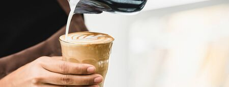 Banner of professional barista pouring steamed milk into coffee glass cup making beautiful latte art Rosetta pattern