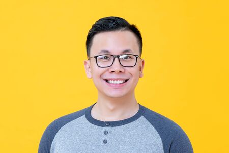Close up portrait of excited smiling young Asian man isolated on yellow background Stock fotó - 145323590