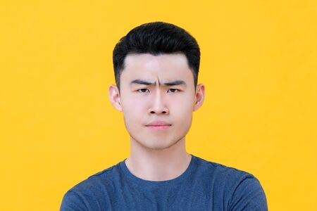 Close up portrait of unhappy angry young Asian man face isolated on yellow background 版權商用圖片
