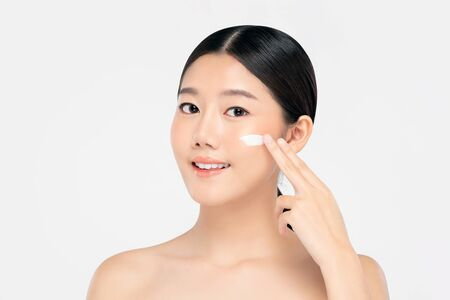 Young beautiful Asian woman with fresh clean appearance applying cream to face isolated on white background for beauty and skin care concepts