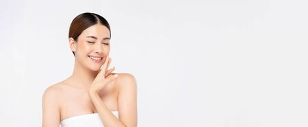 Youthful bright skin smiling pretty Asian woman with hand touching face and eyes closing on white banner background for beauty concepts 写真素材