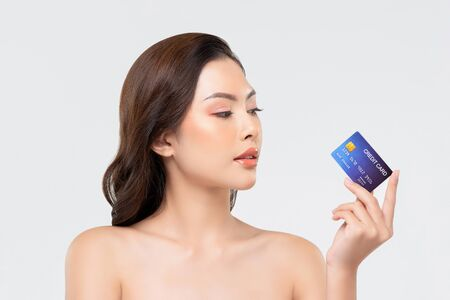 Youthful skin Asian woman showing credit card isolated on white background for beauty treatment promotion and payment concepts