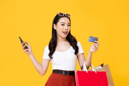 Beautiful smiling Asian woman with shopping bags and smart phone showing credit card in hand isolated on colorful yellow background 版權商用圖片