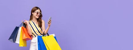 Trendy beautiful young Asian woman carrying colorful bags shopping online with mobile phone isolated on purple banner background Stock fotó