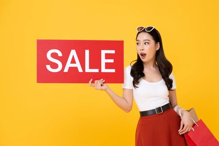 Shocked beautiful Asian woman carrying shopping bags showing red sale sign isolated on yellow background