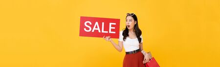 Shocked beautiful Asian woman carrying shopping bags showing red sale sign isolated on yellow banner background Stock fotó
