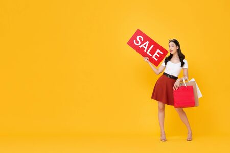 Beautiful Asian woman with shopping bags showing red sale sign isolated on yellow background with copy space Stock fotó