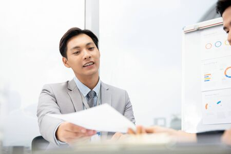 Cheerful Asian businessman suggesting business plan document to client at the meeting in the office