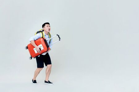 Shocked Asian tourist man holding luggage and looking upward isolated on gray background Stock fotó