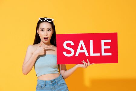 Shocked Asian woman in summer casual clothes pointing to red sale sign in hand isolated on yellow background