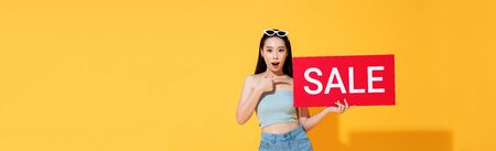 Shocked Asian woman in summer casual clothes pointing to red sale sign in hand isolated on yellow banner background Stock fotó - 145323491
