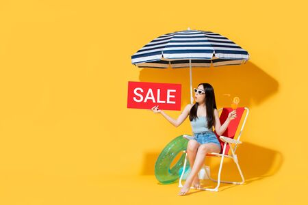 Surprised beautiful Asian woman in summer outfit holding red sale sign while sitting on beach chair isolated on yellow background with copy space 版權商用圖片