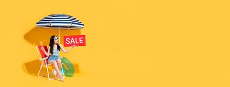 Surprised beautiful Asian woman in summer outfit holding red sale sign while sitting on beach chair isolated on yellow banner background with copy space 版權商用圖片