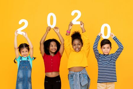 Cute mixed race kids smiling and holding 2020 numbers for new year concept isolated on yellow  background 版權商用圖片