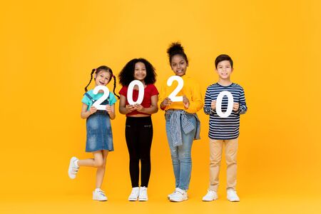 Cute mixed race kids smiling and holding 2020 numbers for new year concept isolated on yellow background 版權商用圖片 - 145323498